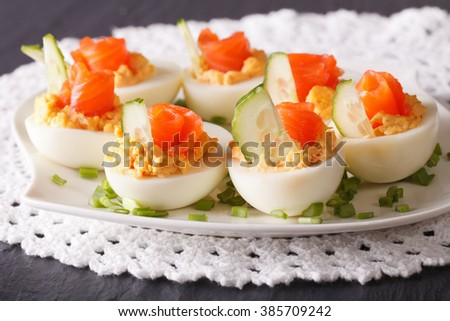 Eggs stuffed with salmon close-up on a plate on the table. horizontal