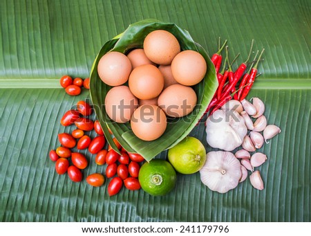 Eggs, tomatoes and spices on banana leaf - stock photo