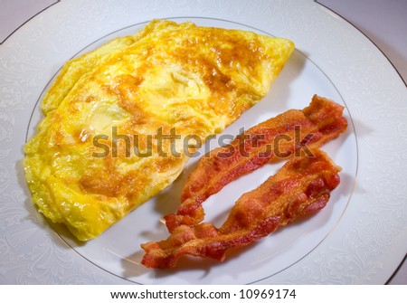 Eggs with bacon on plate ready to eat - stock photo