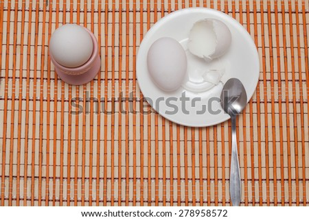 Eggshell, egg and spoon on a white plate.