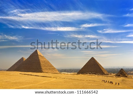 Egypt. Cairo - Giza. General view of pyramids from the Giza Plateau (from left: the Pyramid of Chufu /Cheops/, Khafre, Menkaure /Mykerinos/ and one of the small pyramids known as Queens' Pyramids) - stock photo