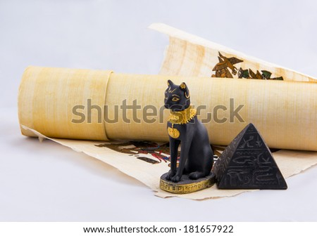 Egyptian cat, a pyramid and papyrus - souvenirs from travels. Objects from a trip to Egypt. - stock photo