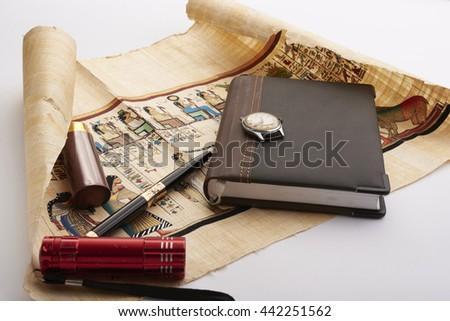 Egyptian papyrus notebook pen flashlight - stock photo