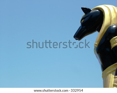 Egyptian Statue against bright blue sky - stock photo