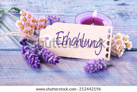 Ehrhohlung - revitalization and wellness background with a handwritten label with the word - Ehrhohlung - in German with a burning aromatherapy candle and fresh lavender on lilac colored wooden boards
