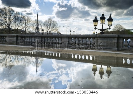 Eiffel Tower and street lamp reflecting in big puddle in Paris, France. This image was taken in Tuileries Garden, close to Place de la Concorde - stock photo