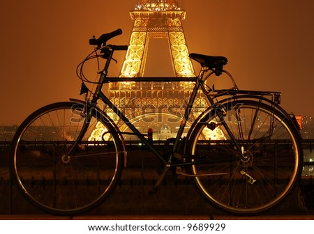 Eiffel tower at night and a bicycle in front of it in Paris - stock photo