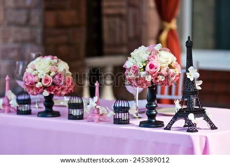 Eiffel tower figurine on a wedding table with white petals, flower bouquets and bird cages on a pink tablecloth. Flowers on a background  - stock photo