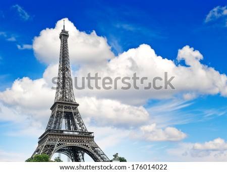 Eiffel Tower (La Tour Eiffel) against cloudy blue sky. Champ de Mars, place of interest in Paris, Europe - stock photo