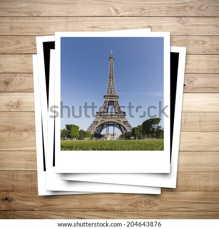 Eiffel Tower memory on photo frame brown wood plank background - stock photo