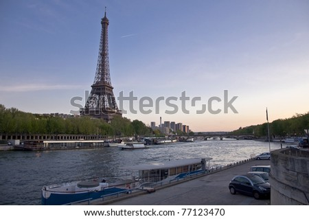 Eiffel Tower on the banks of the River Seine at sunset. Urban night landscape.