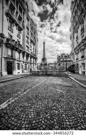 Eiffel Tower seen from the street in Paris, France. Black and white. Free space on cobblestone pavement for your object, text etc. - stock photo