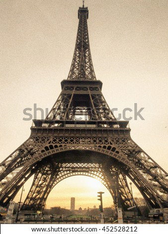 Eiffel Tower (Tour Eiffel ) with morning light through the arch. Close up, vintage, retro aged photo with grain. Paris, France. - stock photo