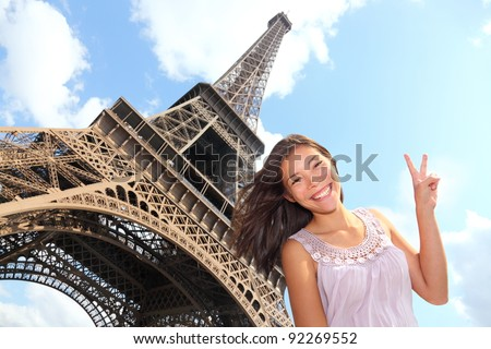 Eiffel Tower tourist posing smiling by Eiffel Tower, Paris, France during Europe travel trip. Young happy excited multiracial Asian Caucasian woman in her 20s. - stock photo