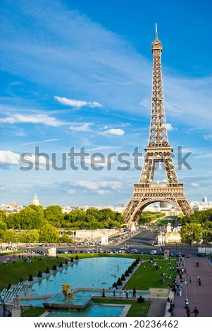 Eiffel Tower, with cloudy blue sky and sunny trees around. - stock photo