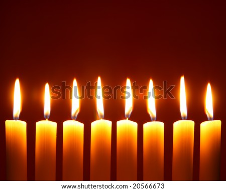 Eight alight candles close-up over red background - stock photo