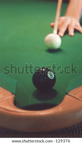 Eight ball lined up one pocket of pool table with man's left  hand lining up pool cue and cue ball.  The table is covered with green simonis cloth, which is very fast and slick, unlike typical felt