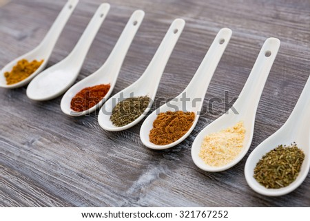 eight ceramic spoons lined up in a line filled with colorful spices on artificial wooden table  - stock photo