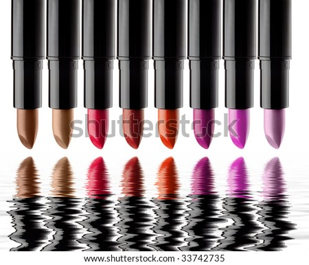 eight colored lipsticks with reflection in water - stock photo