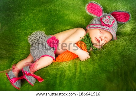Eight day old smiling newborn baby wearing bunny ears and a bunny tail diaper cover. The baby is sleeping on his stomach. - stock photo