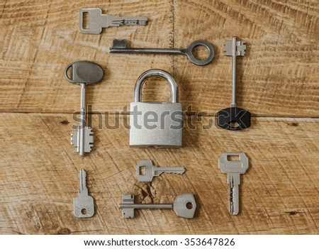 eight different metal keys and one hinged steel padlock on the wooden floor / Many keys one lock