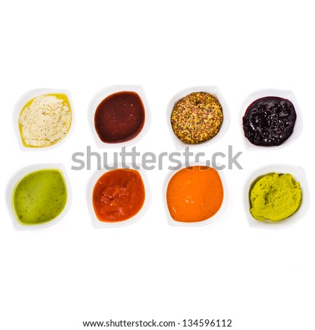 eight different sauces in a white bowls  on the horizontal surface isolated on white background - stock photo