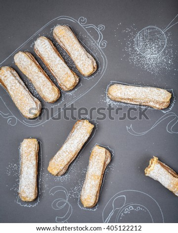 eight eclairs laid out on a background with painted tableware