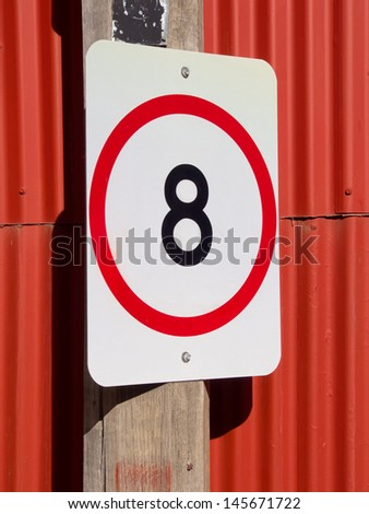 eight km/hr speed restriction sign on red corrugated background  - stock photo