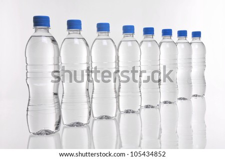 Eight water bottles with blue lids in a row - stock photo