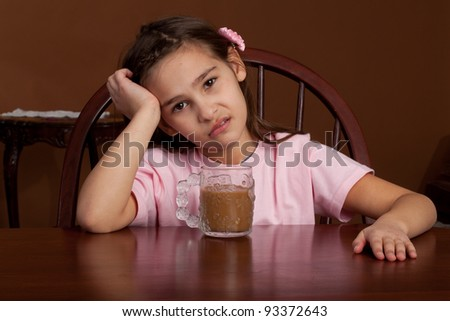 Eight year old girl over a cup of coffee looking sad - stock photo