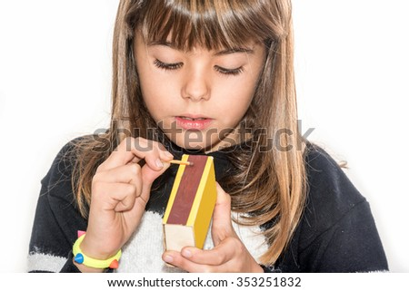 Eight year old girl playing with matches isolated on white - stock photo