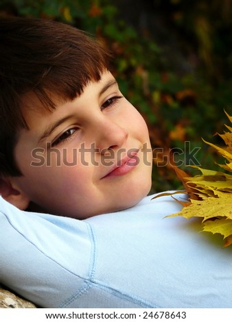 Eight years old boy with autumn leaves - stock photo