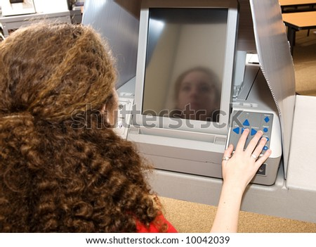Eighteen year old girl voting for the first time on a touch screen machine. - stock photo