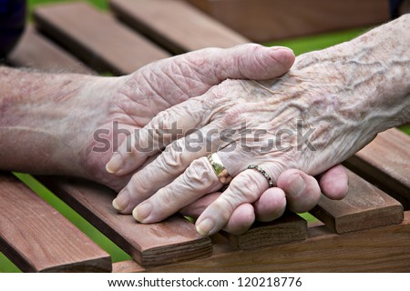 Eighty year old man and woman's hands holding each other - stock photo