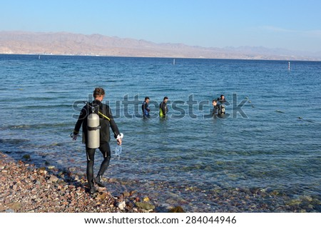 EILAT, ISR - APRIL 15 2015: Divers diving in Coral Beach Nature Reserve in Eilat, Israel.It's one of the most beautiful coral reef in the world and it is visited by travellers from all over the world. - stock photo