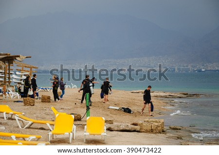 EILAT, ISRAEL - FEBRUARY 22, 2016: People preparing to a dive in Coral Beach Nature Reserve. This one of the most beautiful coral reef in the world is famous tourist and diver attraction. - stock photo