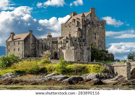 EILEAN DONAN CASTLE, DORNIE, SCOTLAND - SEPTEMBER 20, 2014: close-up in a sunny and bright day with dramatic clouds backdrop. Tourists visit the historic building when touring the Highland and Skye.