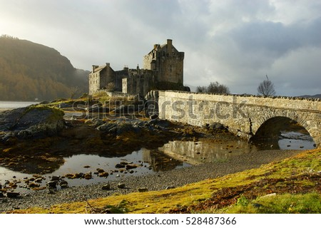 Eilean Donan Castle on lake Loch Duich, Scotland, UK. Sun appears after rainfall. Reflections of the castle in water. Shows the magic of this special place..