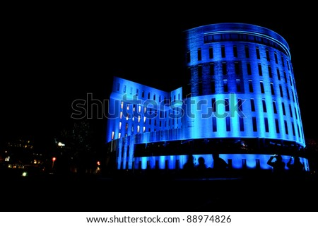 """EINDHOVEN/NETHERLANDS - 10 NOVEMBER-2011: Office building with blue lighting during lightshow """"Glow 2011"""" in Eindhoven at 10-november-2011 - stock photo"""