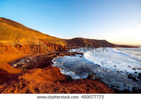 El Golfo bay with fishing boats on the sunset on Lanzarote island in Spain - stock photo