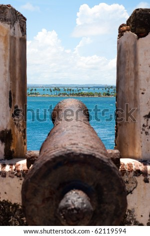 El Morro Fort Cannon covered in rust points out towards the ocean. - stock photo
