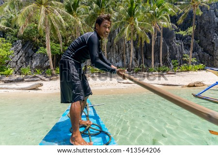 El Nido, Philippines - May 28, 2014: Boatman on a traditional banca boat on the departure from Snake Island, Bacuit Archipelago, El Nido, Palawan, Philippines - stock photo