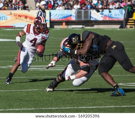 EL PASO, TEXAS - DECEMBER 31.  Virginia Tech�s Andrew Miller (74) blocks UCLA�s Myles Jack (30) as  J.C. Coleman (4) carries the ball at the Sun Bowl on December 31, 2013 in El Paso, Texas.   - stock photo