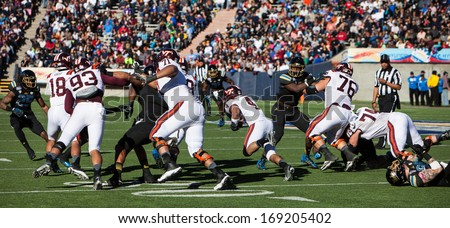 EL PASO, TEXAS -�� DECEMBER 31.  Virginia Tech�s J.C. Coleman (4) finds a hole in the line at the Sun Bowl on December 31, 2013 in El Paso, Texas.    - stock photo