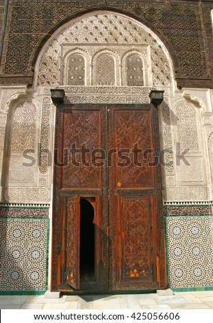 Elaborate door of carved cedar at the Medersa Bou Inania, an ancient madrasa in the Fes el Bali medina in Fez, Morocco - stock photo