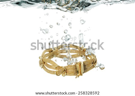 elaborate gold bracelet sinking in water - stock photo