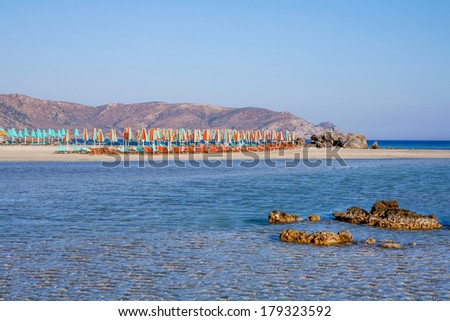 Elafonisos beach with umbrellas and sun loungers on the south-west coast of Crete, Greece. It is rated one of the best beaches in all of Europe and is a protected nature reserve. - stock photo