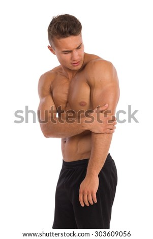 Elbow ache. Young muscular man in holding elbow in pain. Three quarter length studio shot isolated on white. - stock photo