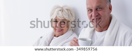 Elder couple is drinking coffee in the bed