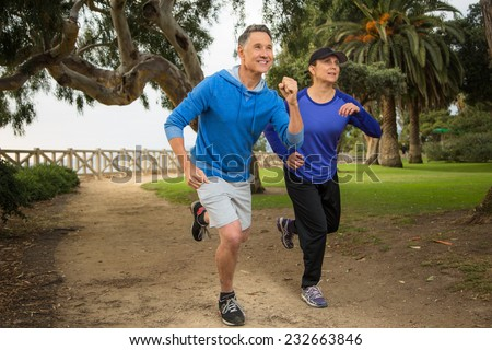 Elder couple running in the park - stock photo